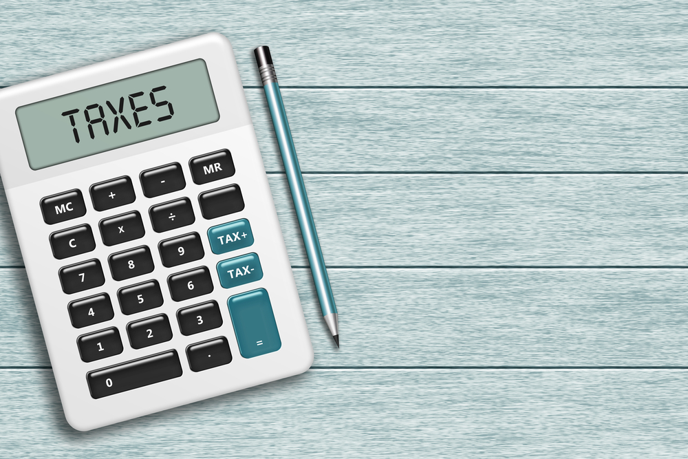 calculator with taxes text lying on wooden desk with place for text